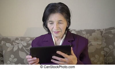 Old business lady looking on a window using tablet, getting flowers of girl