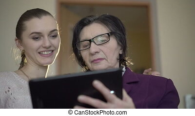 Elegant old business woman and young girl using a tablet on...