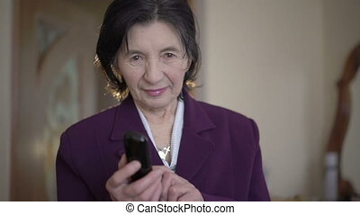Elegant old businesswoman speaking on the phone and smiling...