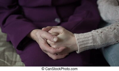 Young girl's hand touches and holds an old woman's wrinkled...