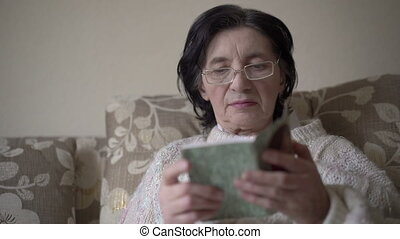 Old woman in glasses reading a prayer book on a sofa.