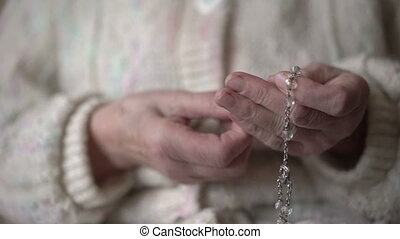 Female hands praying with crystal rosary in full HD