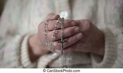 Old wrinkled hands holding rosary and praying with icon -...