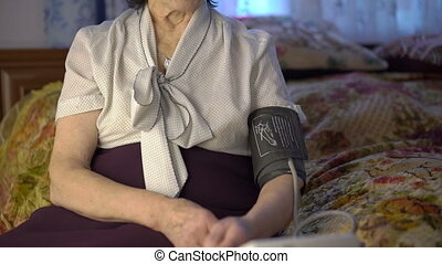 Portrait of old woman in shirt measuring the pressure on hand