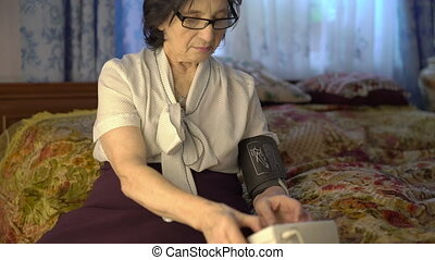 Tired woman put blood pressure measurement tool on her hand.