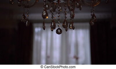 Glow of a crystal chandelier in the background. Slow motion