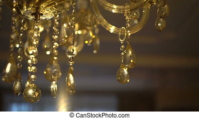Gold crystal chandelier on a bright background. Slow motion.