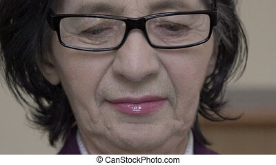 Closeup portrait. Happy old woman in glasses looking down in...