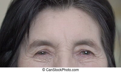 Close up old woman's face, eyes, sincere looking on camera...