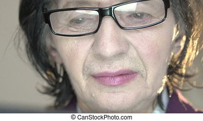 Closeup portrait of mature cute woman in glasses looking down and up