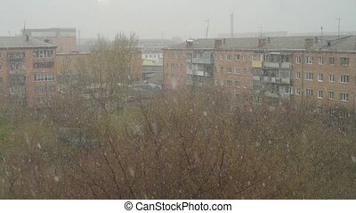 Urban landscape with snowstorm in spring time.