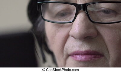 Closeup old business woman's face, glasses, eyes looking on tablet