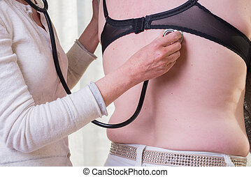 female doctor is listening to lunge of female patient