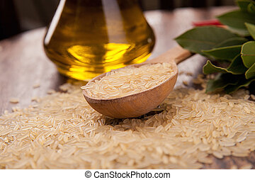 uncooked rice with spoon and woody background - uncooked...