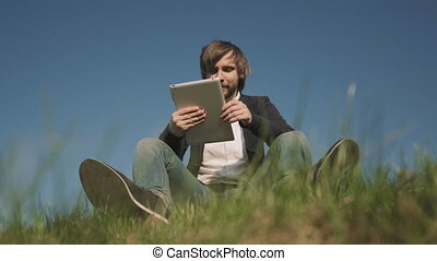 Bottom View of Young Man Talking On Skype Using a Tablet PC Sitting On The Grass