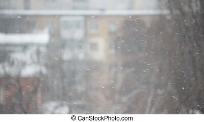 Snow falling in the city on blurred background of apartment...