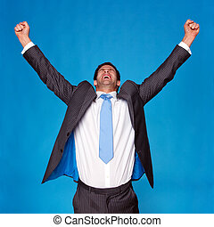 Businessman celebrating with arms raised in the air -...