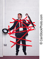 Businessman stuck to wall with red tape - Businessman...