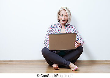 Smiling woman sitting with laptop.