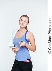 Smiling fitness woman holding bottle with water