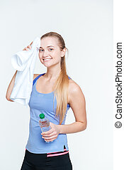 Happy woman holding towel and bottle with water