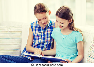 two happy girls reading book at home - people, children,...