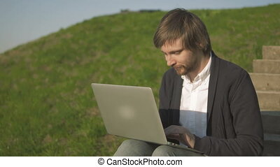 Portrait of Young Man Sitting On The Stairs In Park Using Laptop