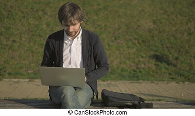 Young Man Sitting On Park Bench, Working On His Laptop,...