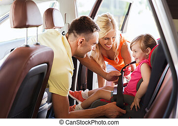 happy parents fastening child with car seat belt - family,...