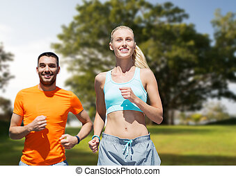 smiling couple running over summer park background -...
