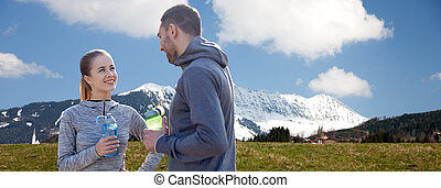 smiling couple with bottles of water outdoors - fitness,...
