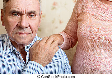 Elderly man looking at the camera - Elderly man and woman...