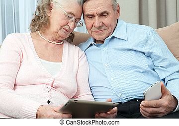 Elderly couple having fun in communicating with family on...