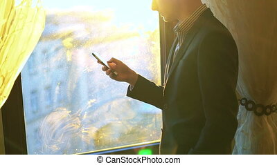 Young businessman using phone and looking through the window