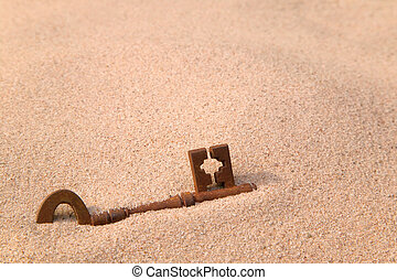 Rusty old key in sand - A rusty old key part buried in sand.