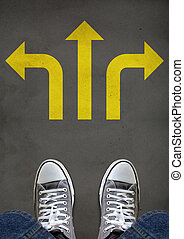 Decision Making Concept - Feet standing on a street mark of...
