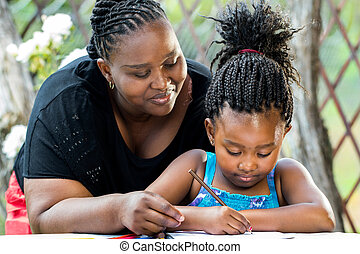 African mother supervising daughter writing. - Close up...