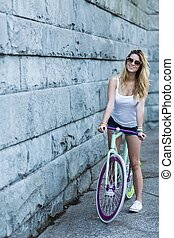 Young girl in the city - Young girl is riding a bike in the...