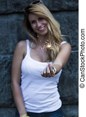 Young girl with a sparkler - Young and pretty girl has a...