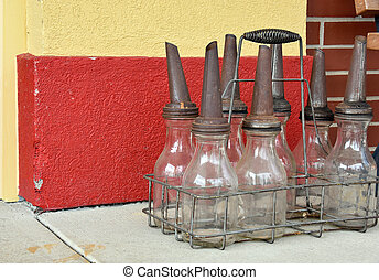 vintage oil bottles in wire rack - Old automotive oil bottle...