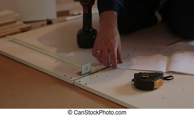 man worker assembles furniture using instructions and a tape...