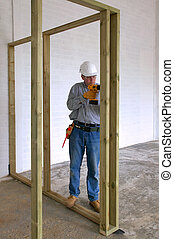 Carpenter drilling into some timber framework in a new house...