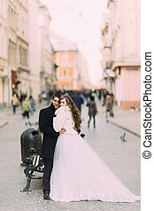 Beautiful married couple standing embracing in the old city with wonderful architecture