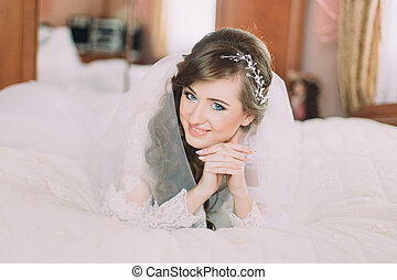 Portrait of beautiful bride in veil with curly hairstyle lying on bed