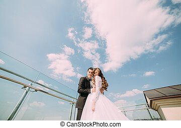 Young bride and groom kissing against blue sky with clouds