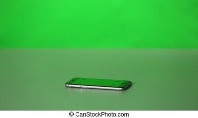 An iPhone and With Green-Screen on a Desk - An iPhone and...