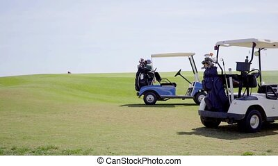 Two golf carts loaded with bags and equipment parked on a...