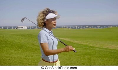 Attractive young woman golfer walking on a course -...