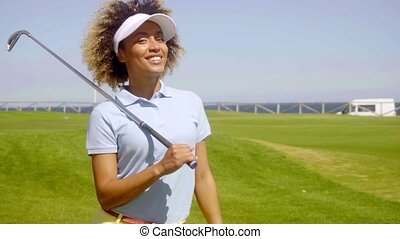 Confident woman enjoying sun while playing golf - Confident...