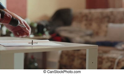 man assembles furniture using a power screwdriver
